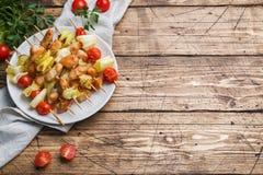 Kebabhöna, zucchini och tomater på steknålar i en platta table trä kopiera avstånd royaltyfri fotografi