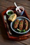 Kebabs用莓果调味汁和香菜在葡萄酒盘子 库存图片