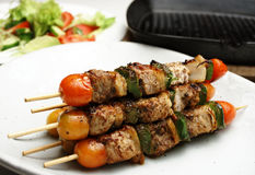 Kebabs. Freshly grilled Shish Kebabs. Grill pan and salad in the background. Shallow depth of field high key shot Royalty Free Stock Photography