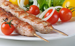 Kebabs. Served with tomatoes and parsley Royalty Free Stock Image