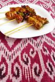 Kebabs asian style fast food. A photograph showing some delicious meat and vegetables kebabs on wooden stick skewers. Meats include chicken and pork while stock photo