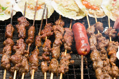 Kebabs cooking on barbecue. Closeup of kebabs and sausage cooking on barbecue grill Stock Image