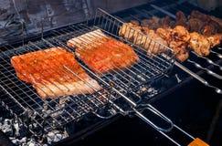 Kebabs de los salmones y del cerdo que asan a la parrilla afuera Imagenes de archivo
