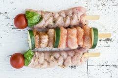 Kebabs des rohen Fleisches auf Aufsteckspindel mit Gemüse Lizenzfreie Stockbilder