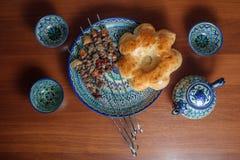 Kebabs en un plato de cerámica y un té negro en tetera pintada Imagen de archivo libre de regalías