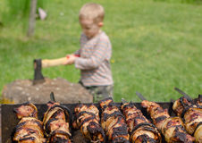 Kebabs grilling on a BBQ as a small boy chops wood Stock Images
