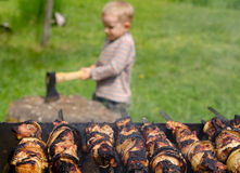 Kebabs grilling on a BBQ as a small boy chops wood Royalty Free Stock Photo