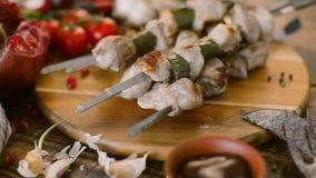Kebabs jugosos del cerdo y de las verduras frescas en un fondo de madera Carne cocinada en un fuego abierto rústico almacen de metraje de vídeo