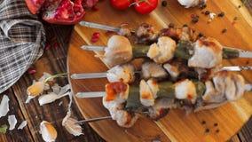 Kebabs jugosos del cerdo y de las verduras frescas en un fondo de madera Carne cocinada en un fuego abierto rústico metrajes