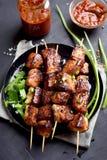 Kebabs on skewers. Kebabs on wooden skewers over dark background, top view Royalty Free Stock Photo