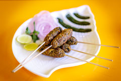 Kebabs. Tempting irresistable Kebabs in sticks  garnished with onions, lime and mint Stock Image