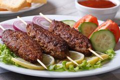 Kebabs on wooden skewers and fresh vegetables on a plate. Kebabs on wooden skewers with ketchup and fresh vegetables on a plate close-up. horizontal Royalty Free Stock Photography