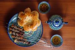 Kebabs y pan asiático en un plato de cerámica Fotos de archivo