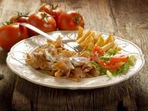 Kebap con la ensalada y las patatas encendido Imagenes de archivo