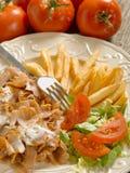 Kebap con la ensalada y las patatas encendido Fotos de archivo libres de regalías