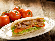Kebap sandwich on dish. On wood background Royalty Free Stock Photo