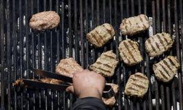 Chopped meat kebapcheta, meatballs, charcoal grill. Kebapcheta and meatballs on charcoal grill, human hand with grill tongs Stock Photo