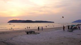 KEDAH, LANGKAWI, MALASIA - 8 de abril de 2015: Turistas que tienen momento romántico durante puesta del sol en la playa de Cenang imagenes de archivo