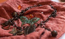 Kedja med dekorativa sidor, pärlor, fjärilar på röd cloch royaltyfri fotografi