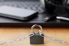Kedja med låset som är främst av bärbara datorn och smartphonen, grej och digitalt apparatdetoxbegrepp arkivfoton