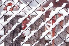 Kedja-sammanlänkning fäktning som täckas av snö Arkivfoton
