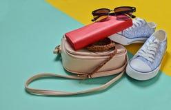 Keds, lunettes de soleil, ceinture, bourse, sac sur un fond en pastel jaune bleu Femmes et x27 ; accessoires de s Tendance de min Image libre de droits