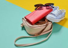 Keds, sunglasses, belt, purse, bag on a blue yellow pastel background. Women& x27;s accessories. Trend of minimalism. Keds, sunglasses, belt, purse, bag on a Royalty Free Stock Images