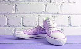 Keds with white laces close-up on wooden flloor against a white brick wall. stock image