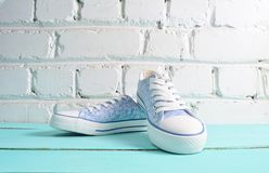 Keds with white laces close-up on wooden flloor against a white brick wall. royalty free stock image