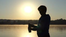 Keeeps de la mujer un frasco con café en la puesta del sol en 4k almacen de metraje de vídeo