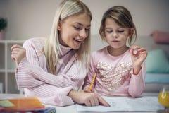 Keek haar Moeder en dochter het werk thuiswerk stock afbeeldingen