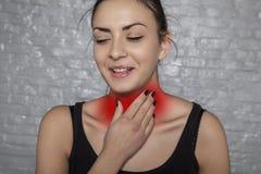Keel besmet met bacteriën, een vrouw die haar keel houden stock fotografie