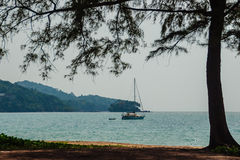 Keel boat moored at shore side, view from forest beach. Seascape Stock Photography