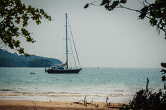Keel boat moored at shore side, view from forest beach. Seascape Royalty Free Stock Image