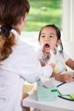 Keelonderzoek op het kantoor van de pediater Stock Afbeelding