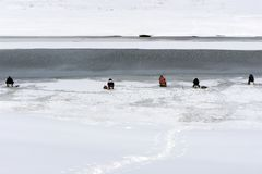 Keen fisherman catches fish in the winter in the hole made in the ice covering the river bed. Next to the fisherman melt the ice a royalty free stock images