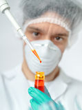 Keen scientist with brown eyes pipettes orange sample. Keen scientist with brown eyes in protective wear pipettes orange sample, Shallow DOF, focus on pilette Stock Photos