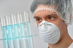 Keen scientist in protective wear performs protein assay. Shallow DOF, focus on the tubes and gloved hand royalty free stock photo
