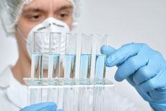 Keen scientist in protective wear performs protein assay. Shallow DOF, focus on the tubes and gloved hand stock photos