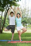 Keep balance. Vertical image of happy young people keeping balance in a yoga pose Royalty Free Stock Images