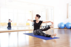 Keep the balance. Portrait of a middle age woman doing yoga at the yoga studio Stock Images