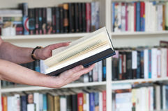 Keep book in hand. Women´s hands holding a book in his hand in front of a bookshelf Stock Image