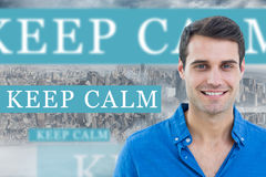 Keep calm against room with large window looking on city. The word keep calm and handsome man smiling to the camera against room with large window looking on royalty free stock photography