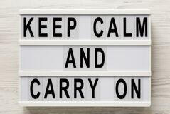 `Keep Calm And Carry On` Words On A Lightbox On A White Wooden Background, Top View. Overhead, From Above, Flat Lay Royalty Free Stock Photo