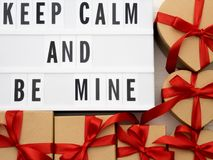 KEEP CALM AND BE MINE word on lightbox on knit background with wrapped gifts boxes. Valentine`s day concept. Royalty Free Stock Photography