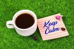 Keep calm with coffee. Keep calm word in memo with coffee cup , coffee bean and dried rose bud on grass Royalty Free Stock Image