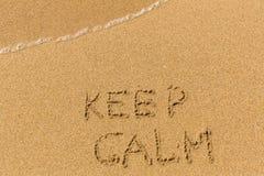 Keep Calm -  drawn on the sand beach Royalty Free Stock Photos