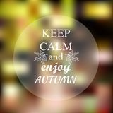 Keep calm and enjoy autumn phrase on orange blur Stock Photos