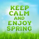 Keep calm and enjoy spring poster. Spring inscription made of grass. Spring background with green early spring grass on blurred soft background. Grassland Stock Image