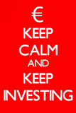 Keep Calm and Keep Investing. A take on the Keep Calm and Carry on War Time Poster.  The words Keep Calm and Keep Investing written in white against a red Stock Photo